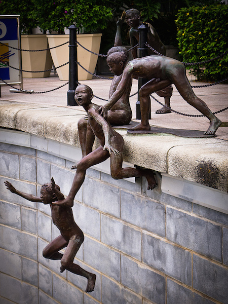 sculpture of 5 people jumping in river singapore