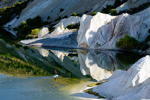 photograph of people paddle boarding on a lake in New Zealand