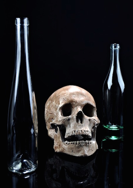 still life photography set up with skull and bottles