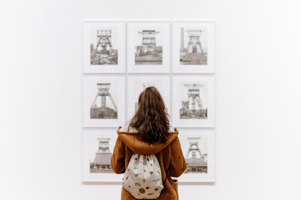 Image of a potential buyer viewing art in a live exhibition
